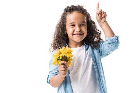 happy african american girl holding yellow flowers and pointing up with finger isolated on white