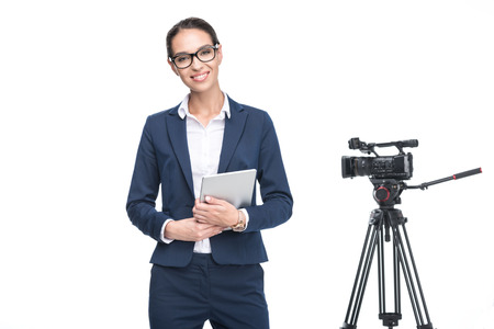 smiling female television reporter using digital tablet standing near video camera, isolated on white