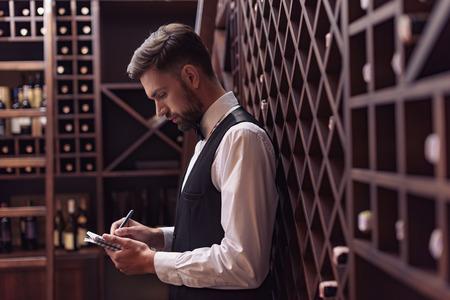 Portrait of young handsome sommelier in Wine cellar Banco de Imagens