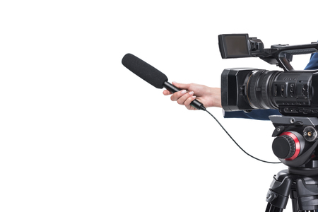 cropped view of video camera and female hand with microphone, isolated on white