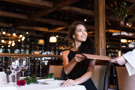 Young beautiful woman taking menu from waiter in restaurant Stock Photo