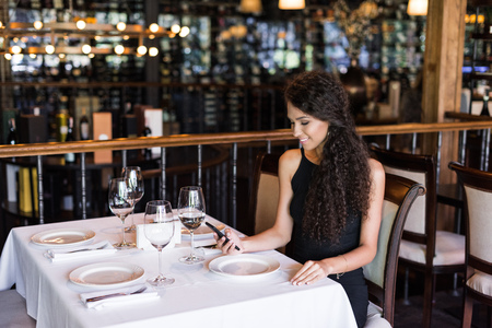 Portrait of young beautiful woman using smartphone while sitting at table in restaurant