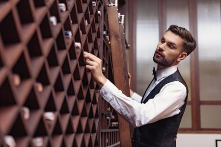 Porträt des jungen gutaussehenden Sommeliers, der Wein im Keller wählt