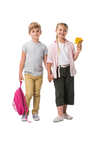 happy adorable children holding backpack and yellow flowers while standing together and holding hands isolated on white 版權商用圖片