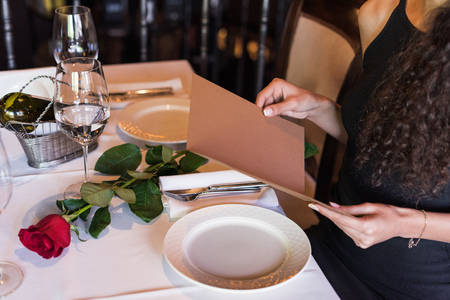 Cropped view of woman with menu sitting at table in restaurant