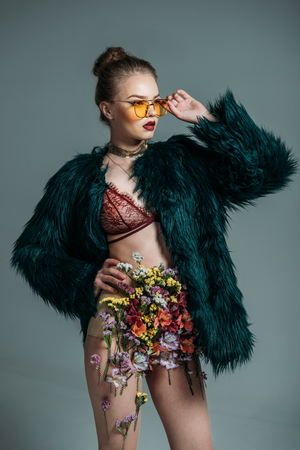 young attractive model posing in floral skirt, lace bra, green fur coat and orange sunglasses for  fashion shoot, isolated on grey Stock Photo