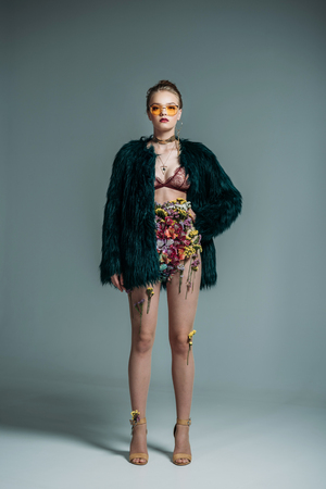 young attractive model posing in floral skirt, lace bra and green fur coat for  fashion shoot on grey