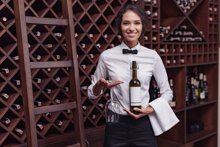 Portrait of young beautiful woman sommelier standing with bottle of wine and glass in cellar
