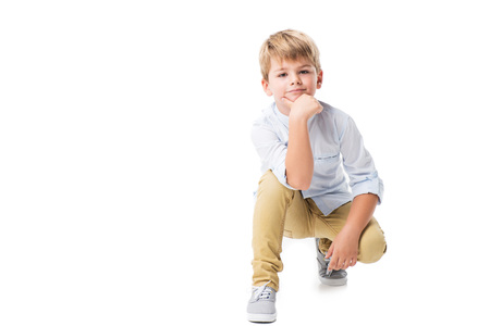 adorable little boy kneeling and looking at camera isolated on white