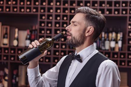 Portrait of handsome waiter drinking wine from bottle in cellar