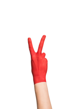 cropped view of hand in red paint showing peace symbol, isolated on white Foto de archivo - 102256079
