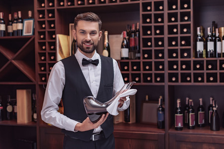 Portrait of handsome sommelier holding decanter with red wine in cellar
