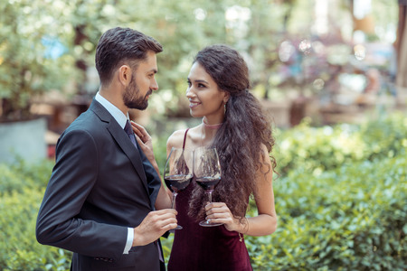 Happy young coupe standing with red wine in garden