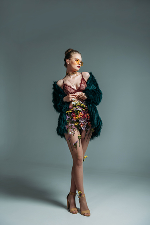young attractive girl posing in floral skirt, lace bra and green fur coat for  fashion shoot on grey Standard-Bild - 102893723