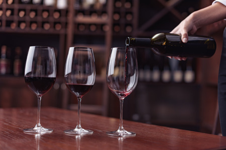 Cropped view sommelier pouring red wine from bottle into glass at table in cellar Imagens