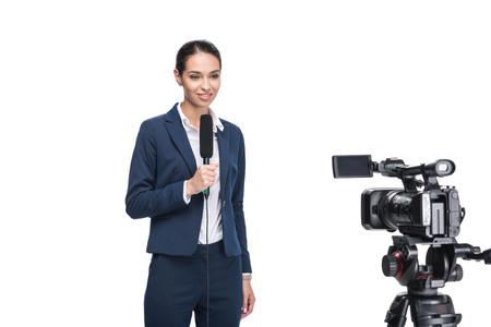 mooie glimlachende vrouwelijke journalist met microfoon kijken camera, geïsoleerd op wit