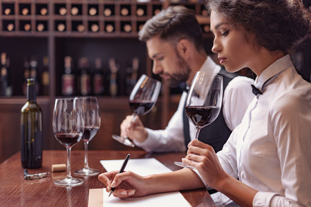 Two sommeliers, male and female tasting red wine and making notes at degustation card Foto de archivo