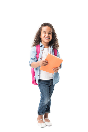 beautiful african american schoolgirl holding textbook and smiling at camera isolated on white