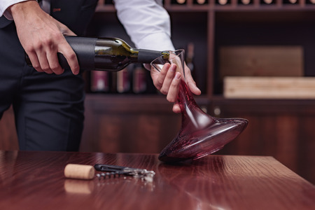 Cropped view sommelier pouring red wine from bottle into decanter at table in cellar Banco de Imagens
