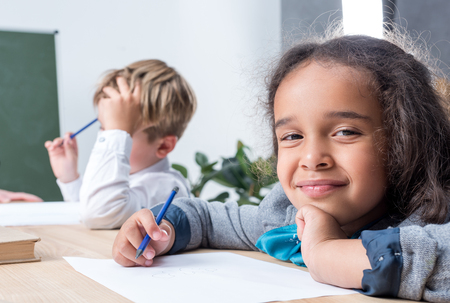 cute multiethnic schoolkids drawing while sitting at desk in class Imagens