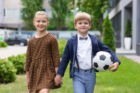 adorable schoolgirl and schoolboy with soccer ball holding hands and smiling at camera 免版税图像