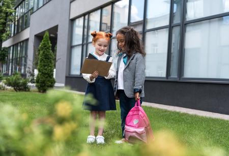 happy multiethnic schoolgirls reading book together while standing near school