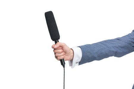 cropped view of male hand holding microphone for interview, isolated on white
