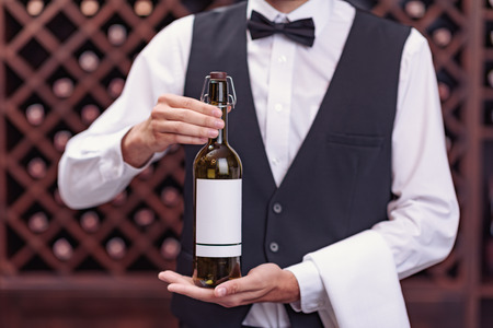 Cropped view man sommelier holding bottle of wine in cellar