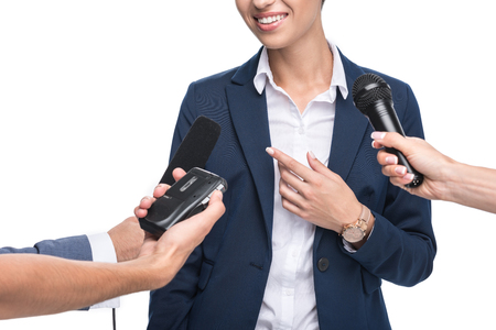 cropped view of journalists with microphones and recorder interviewing smiling businesswoman, isolated on white Stock Photo