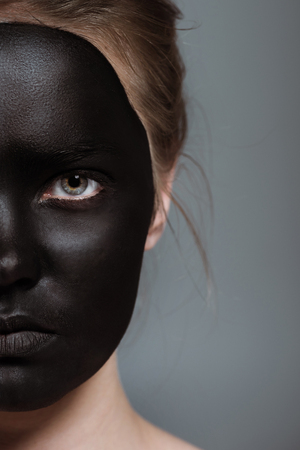 cropped view of girl with creative black bodyart on face, isolated on grey