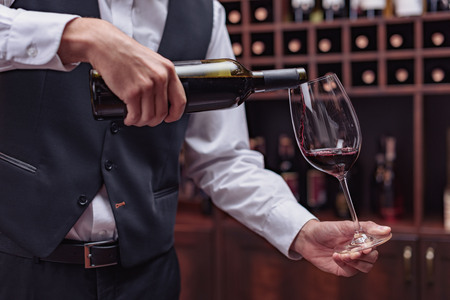 Cropped view sommelier pouring red wine from bottle into glass at table in cellar Stock Photo