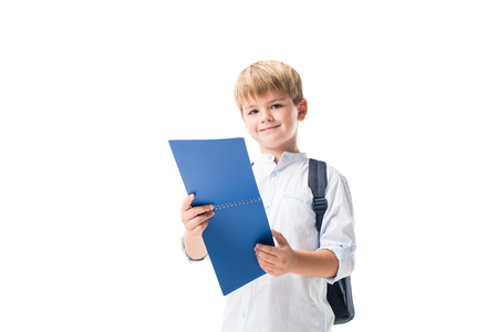 cute smiling schoolboy holding notebook and looking at camera isolated on white