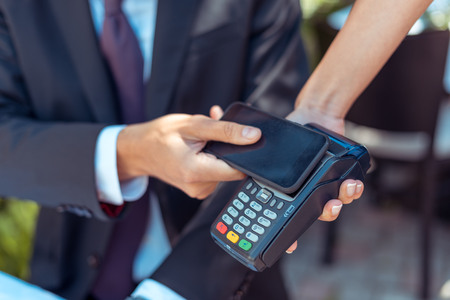 Close-up view man paying with NFC technology on smartphone