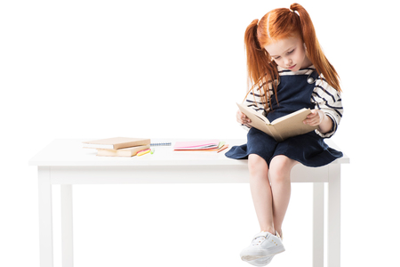 adorable schoolgirl reading book while sitting on table isolated on white Stock Photo