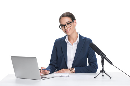 attractive smiling female newscaster sitting at table with laptop, notepad and microphone, isolated on white  Stock Photo