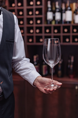 Cropped view sommelier holding empty wine glass in cellar