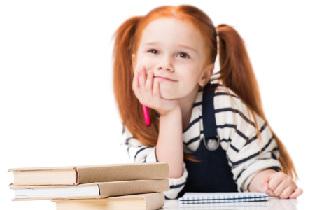 pensive smiling redhead schoolgirl drawing with felt tip pen while sitting at desk with books