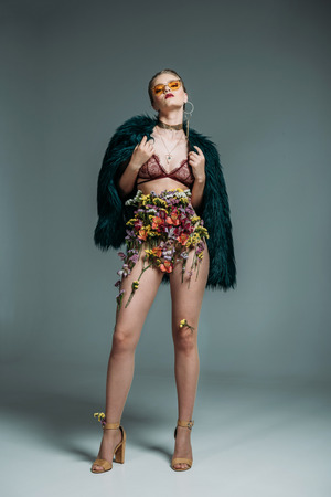 young seductive beautiful model posing in floral skirt, lace bra, green fur coat and orange sunglasses for fashion shoot, on grey