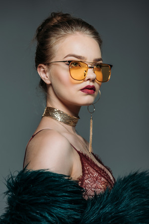 young trendy attractive model posing in lace bra, green fur coat and orange sunglasses for fashion shoot, isolated on grey Stock Photo