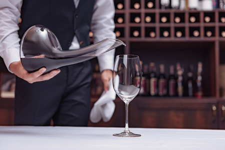 Cropped view sommelier pouring red wine from decanter into glass at table in cellar Banco de Imagens