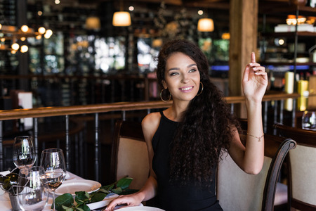 Portrait of young beautiful woman with raised hand calling waiter in restaurant