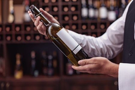 Cropped view man sommelier holding bottle of wine in hands