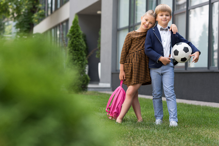 beautiful happy schoolboy and schoolgirl with backpack and soccer ball smiling at camera near school 写真素材 - 102358426