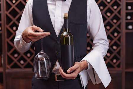 Cropped view sommelier holding bottle of wine and glass in cellar
