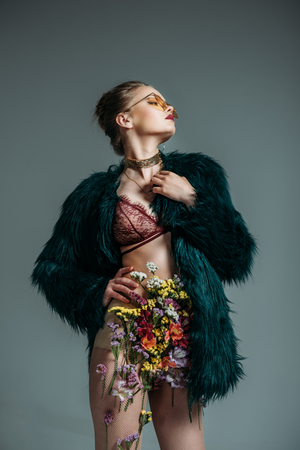 young sensual model posing in floral skirt, lace bra and green fur coat for  fashion shoot, isolated on grey