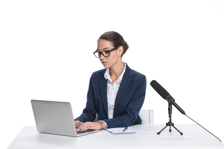 attractive female newscaster sitting at table with laptop, notepad and microphone, isolated on white  Stock Photo