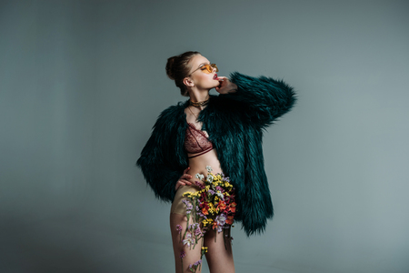 young attractive model posing in floral skirt, lace bra and green fur coat for  fashion shoot, isolated on grey