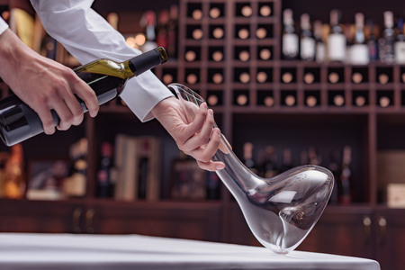 Cropped view sommelier pouring red wine from bottle into decanter at table in cellar Stock Photo