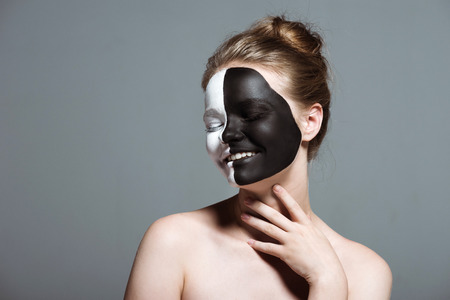 young smiling model with creative white and black bodyart on face, isolated on grey Stockfoto