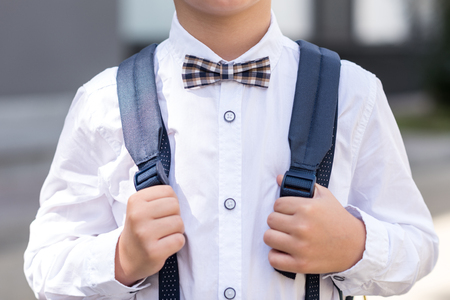 cropped shot of stylish schoolboy wearing bow tie holding backpack  Stock Photo